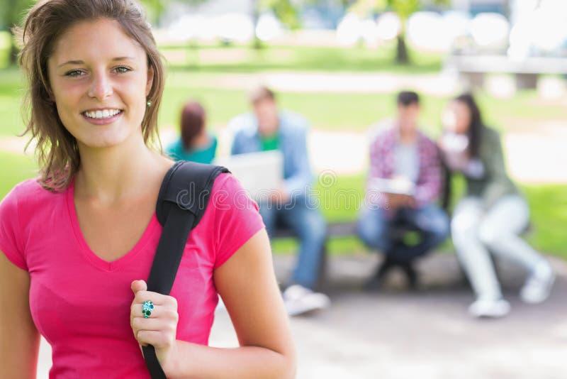 Estudiante universitaria que sonríe con los estudiantes borrosos en parque fotografía de archivo