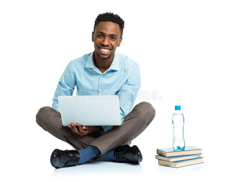 Estudiante universitario afroamericano feliz que se sienta con el ordenador portátil en wh foto de archivo libre de regalías