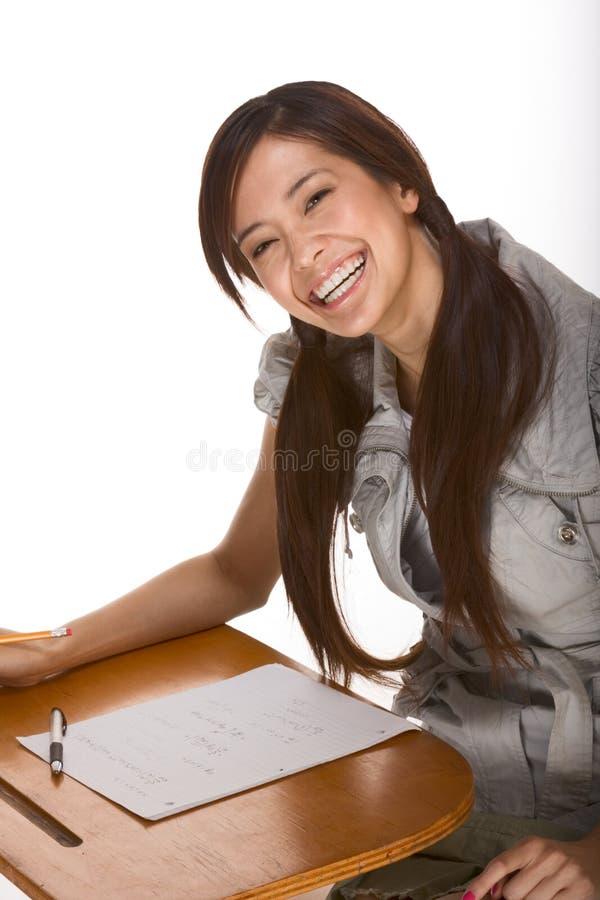 Estudiante universitario asiático emocionado cómodo por el escritorio fotos de archivo libres de regalías