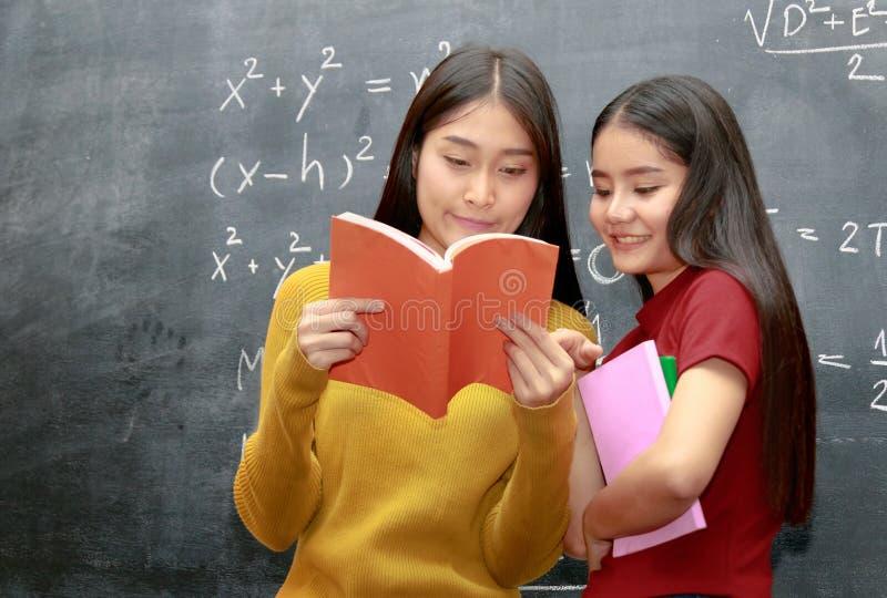 Estudiante universitario asiático feliz dos sobre los libros de lectura de la pizarra fotografía de archivo libre de regalías