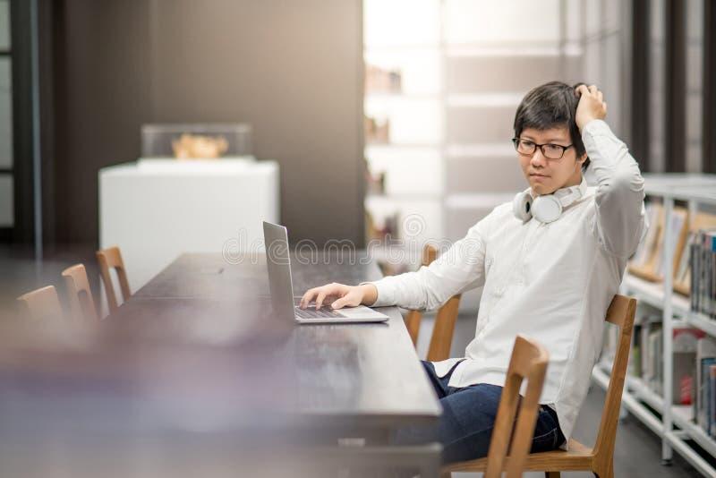 Estudiante universitario asiático joven que trabaja en biblioteca imagen de archivo