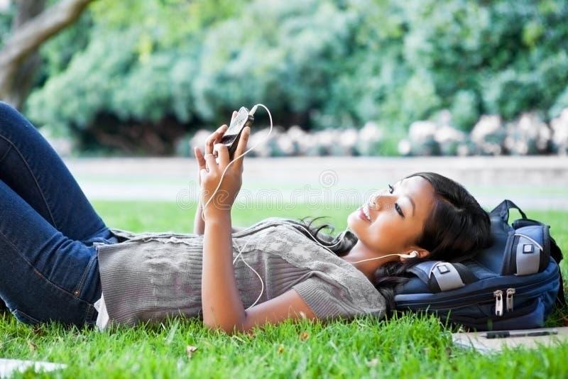 Estudiante universitario asiático que escucha la música foto de archivo