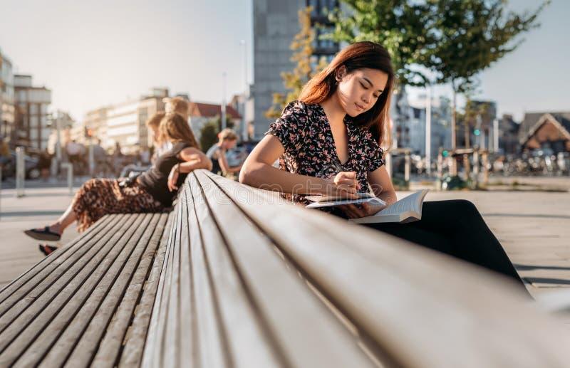 Estudiante universitario asiático que se sienta en estudiar del banco del campus imagen de archivo libre de regalías