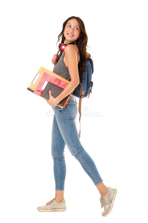 Estudiante universitario asiático sonriente integral que camina contra fondo blanco aislado con los libros y el bolso imagenes de archivo