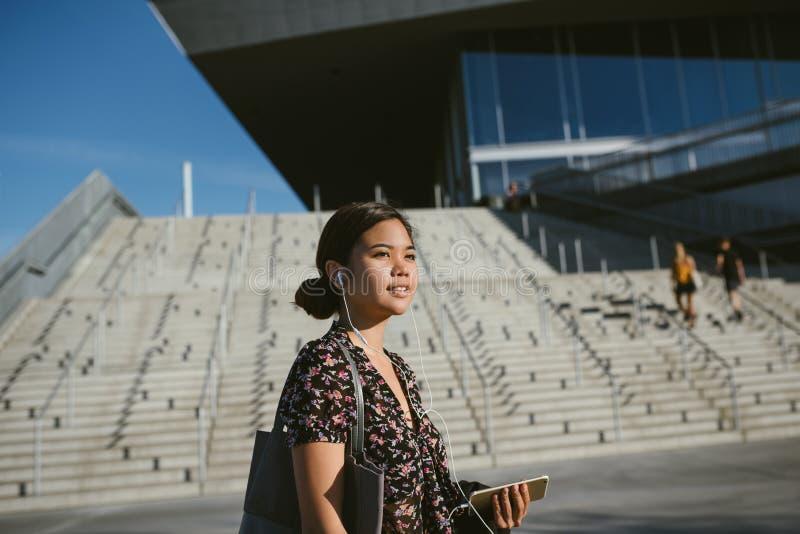 Estudiante universitario asiático sonriente que camina en el campus que escucha la música imagen de archivo libre de regalías