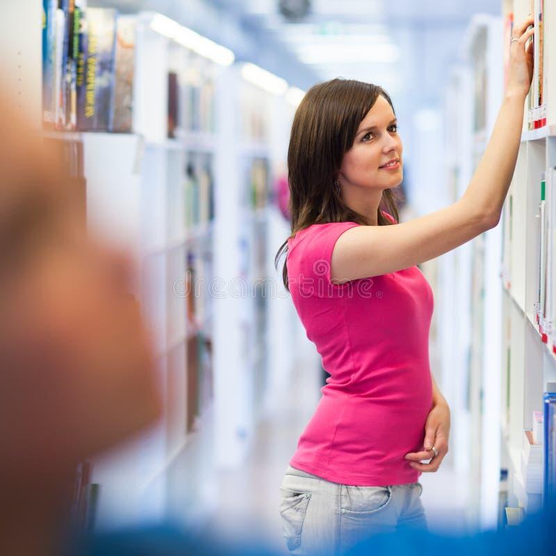 Estudiante universitario bastante joven en una biblioteca foto de archivo libre de regalías