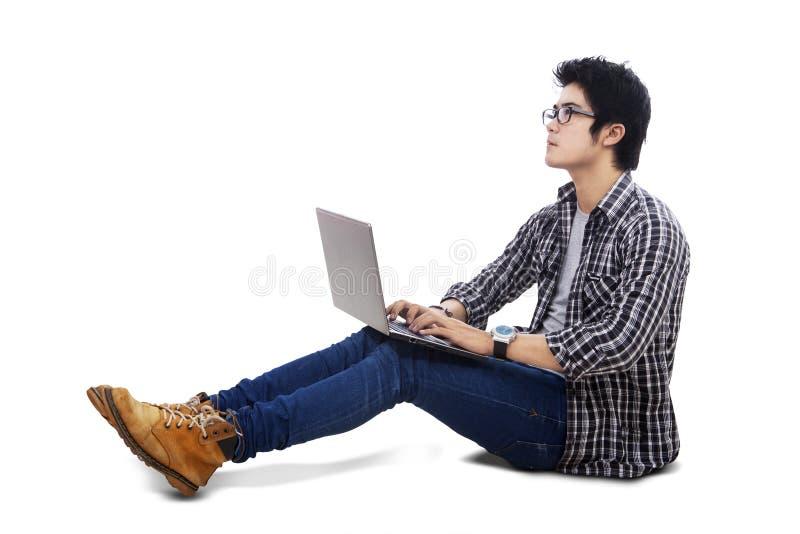 Estudiante universitario con el ordenador portátil que mira el copyspace fotografía de archivo