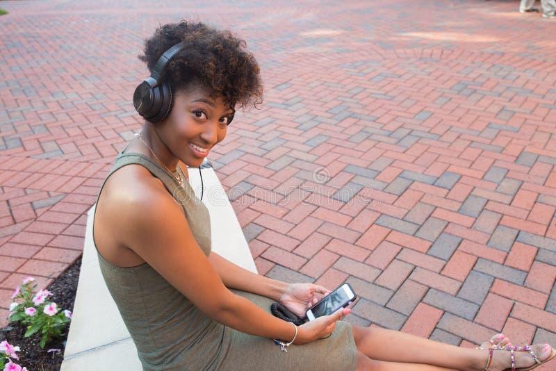 Estudiante universitario con los auriculares y mirada de un teléfono celular fotos de archivo