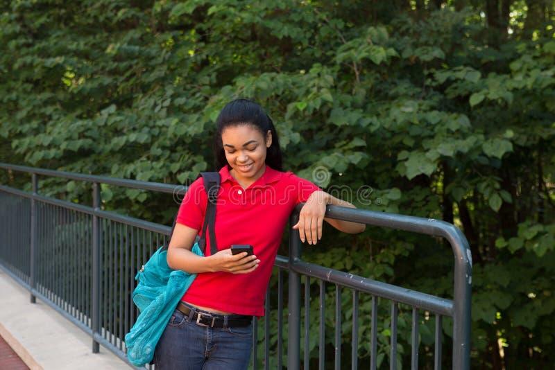 Estudiante universitario con una mochila que mira su teléfono celular fotos de archivo