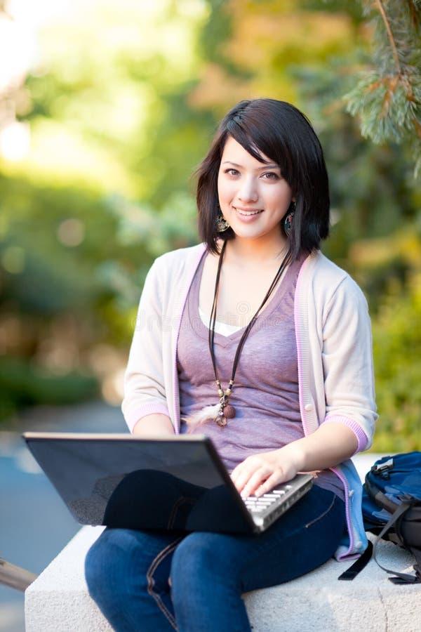 Estudiante universitario de la raza mezclada con la computadora portátil imágenes de archivo libres de regalías
