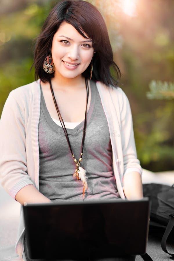 Estudiante universitario de la raza mezclada con la computadora portátil imagen de archivo libre de regalías