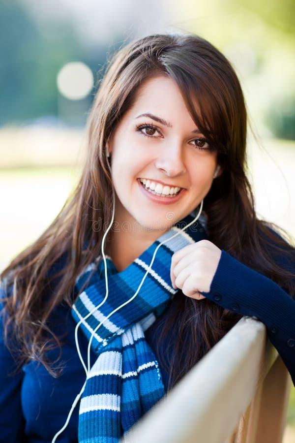 Estudiante universitario de la raza mezclada que escucha la música imagen de archivo libre de regalías