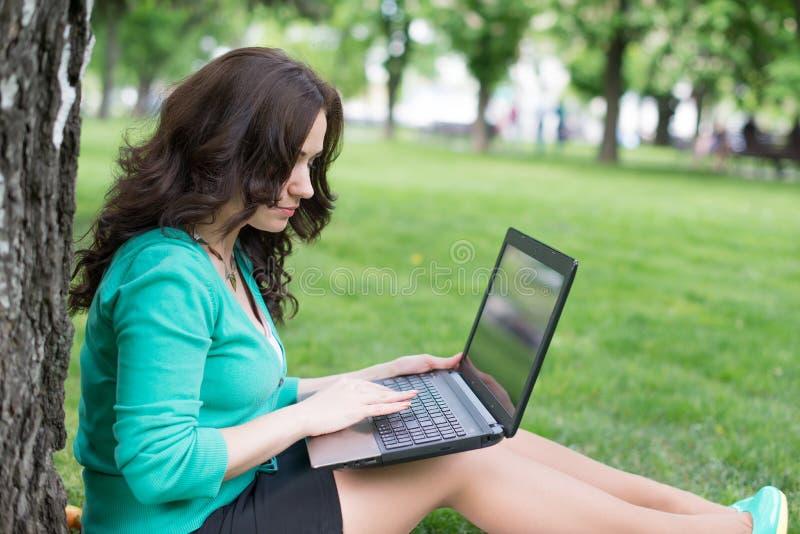 Estudiante universitario de la raza mixta que se sienta en el funcionamiento de la hierba imagen de archivo