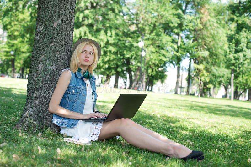 Estudiante universitario de la raza mixta que se sienta en el funcionamiento de la hierba fotografía de archivo libre de regalías