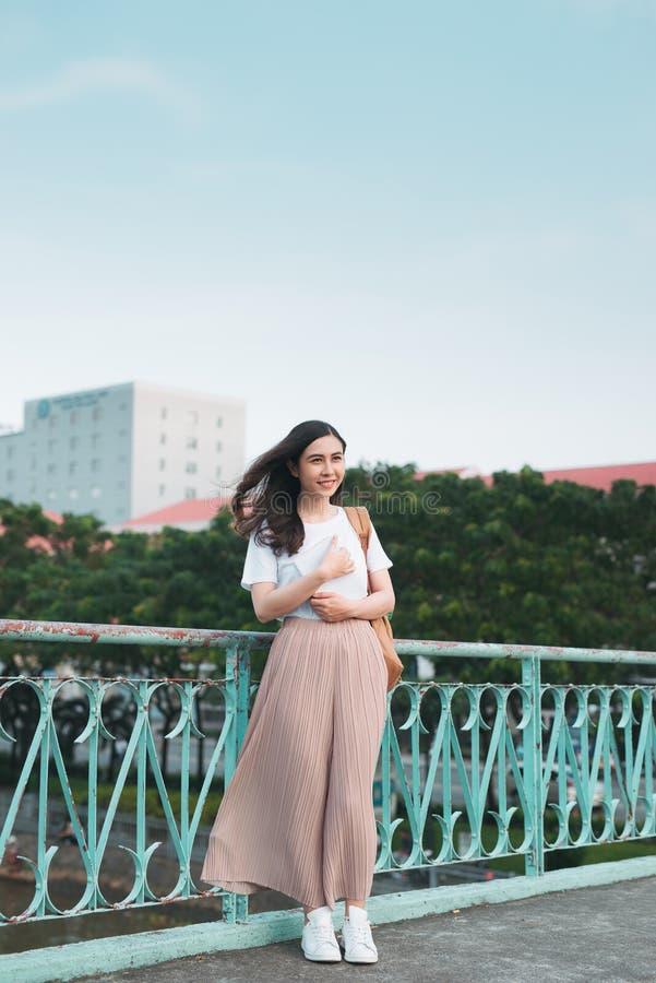 Estudiante universitario de sexo femenino asiático hermoso que sostiene sus libros que se colocan al aire libre, concepto de la u fotos de archivo libres de regalías