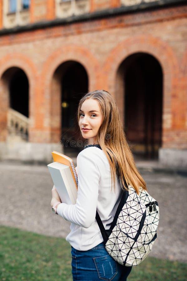 Estudiante universitario de sexo femenino elegante con el bolso y libros en campus al aire libre imagen de archivo
