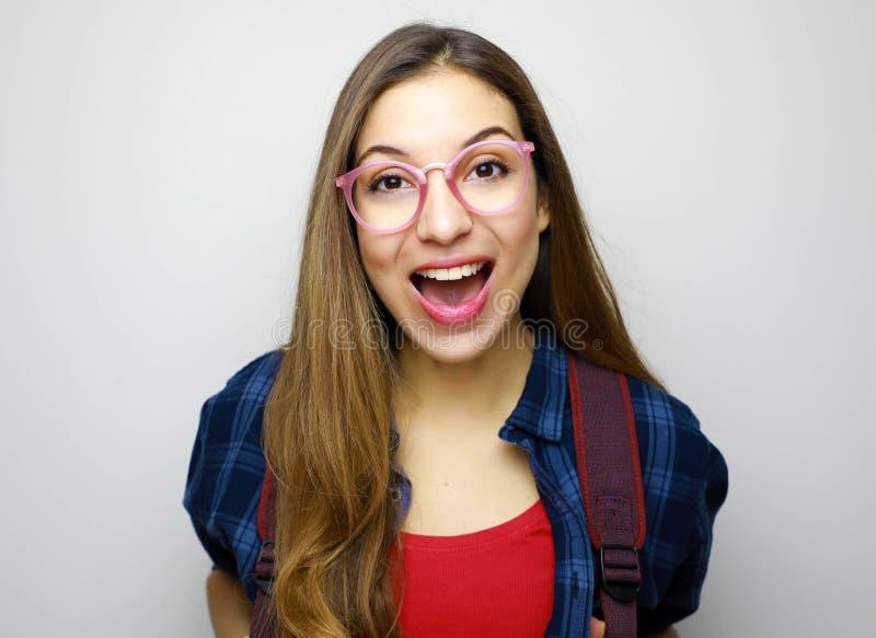 Estudiante universitario de sexo femenino emocionado de la universidad aislado en el fondo blanco Mujer joven sorprendida del est imagen de archivo libre de regalías