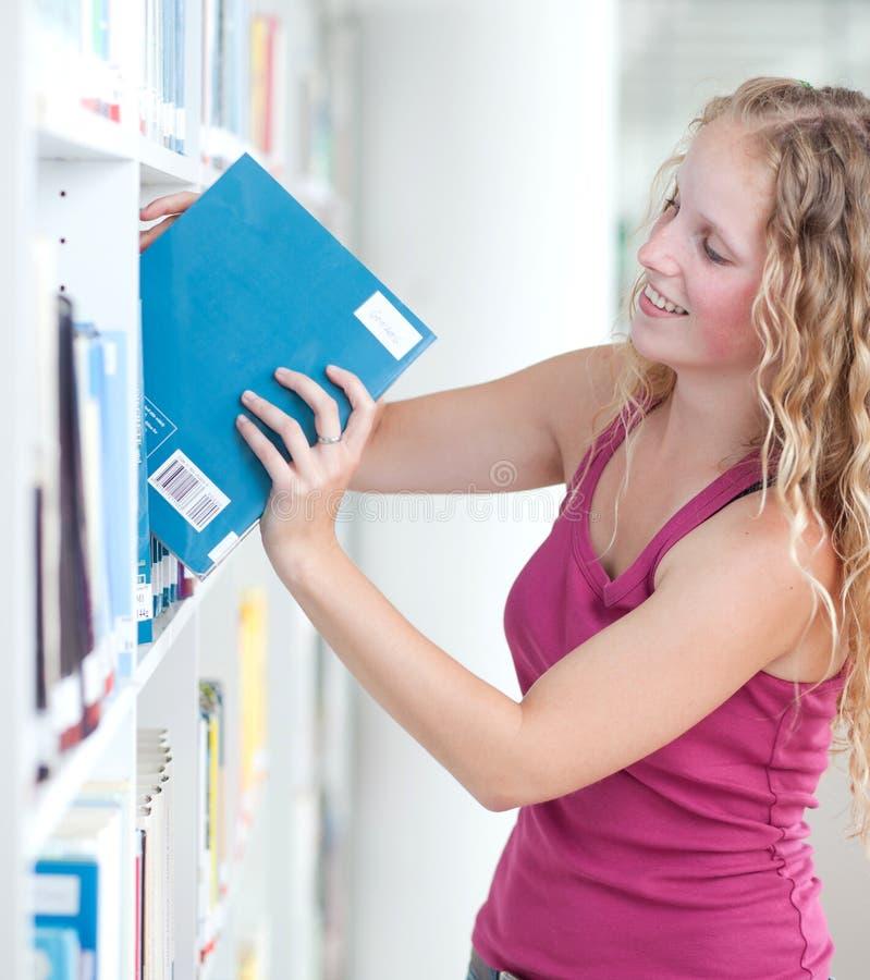 Estudiante universitario de sexo femenino en una biblioteca foto de archivo libre de regalías