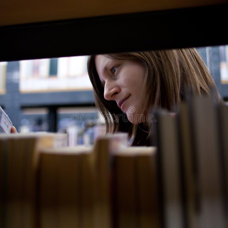 Estudiante universitario de sexo femenino en una biblioteca fotos de archivo libres de regalías