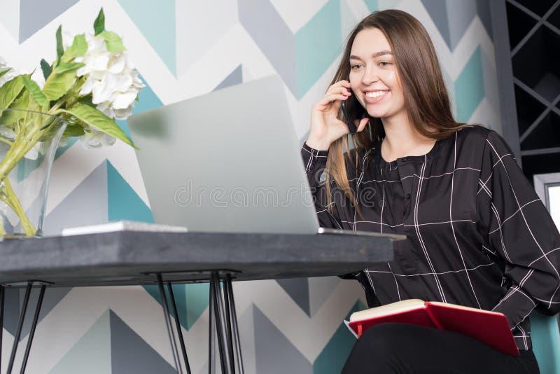 Estudiante universitario de sexo femenino feliz que aprende en línea vía el ordenador portátil y que habla en el teléfono móvil foto de archivo