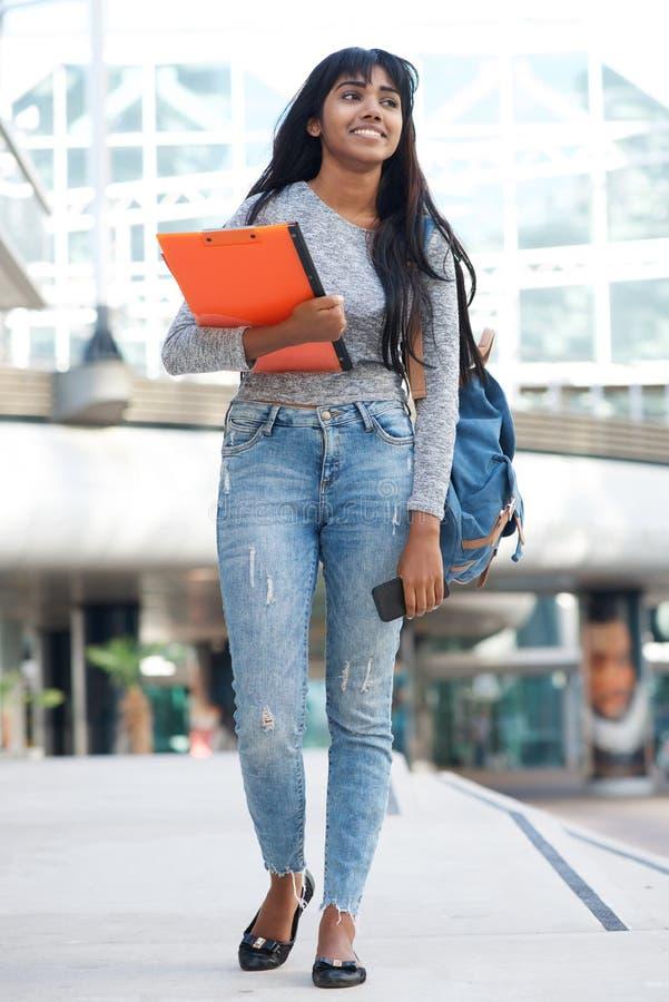 Estudiante universitario de sexo femenino indio del cuerpo completo que camina en ciudad con los libros y el bolso fotografía de archivo