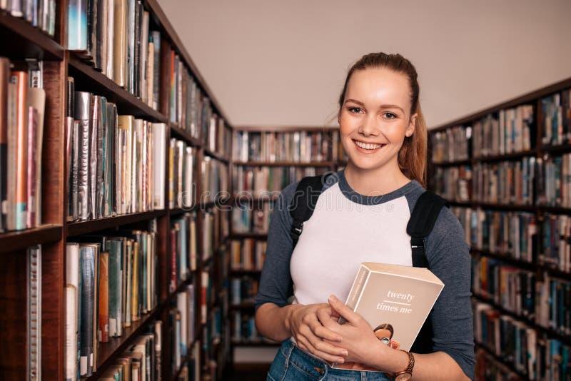 Estudiante universitario de sexo femenino joven en biblioteca foto de archivo