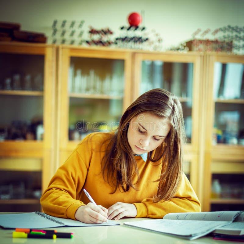 Estudiante universitario de sexo femenino joven en la clase de química, escribiendo notas Estudiante enfocado en sala de clase fotos de archivo libres de regalías