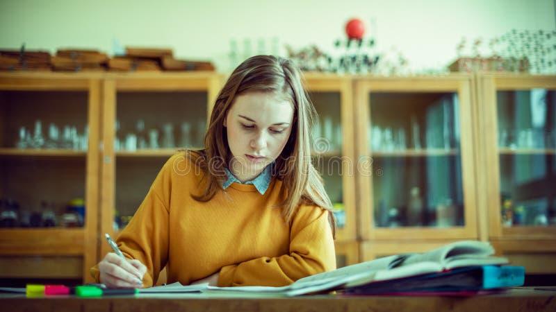 Estudiante universitario de sexo femenino joven en la clase de qu?mica, escribiendo notas Estudiante enfocado en sala de clase Co fotografía de archivo