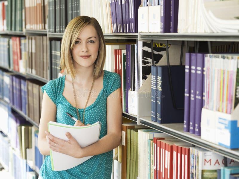 Estudiante universitario de sexo femenino In Library imágenes de archivo libres de regalías