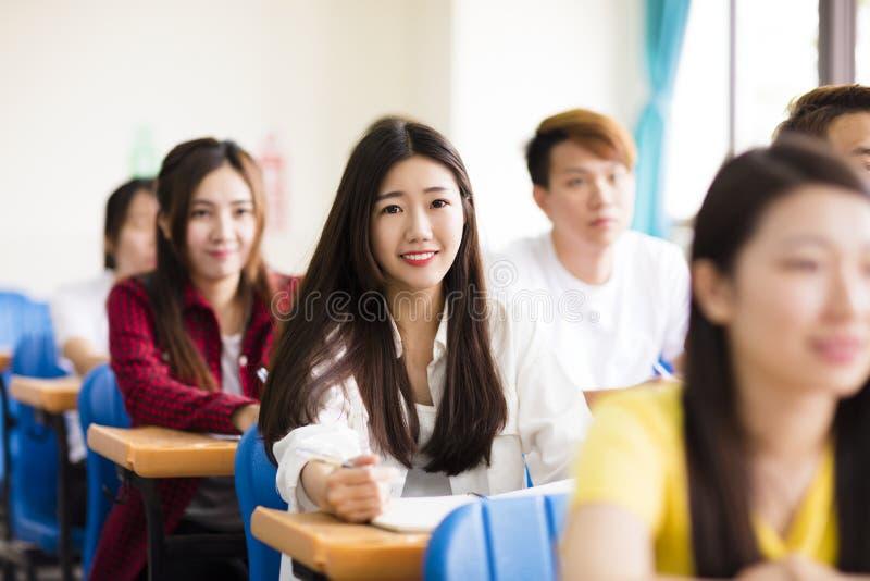 estudiante universitario de sexo femenino que se sienta con los compañeros de clase foto de archivo libre de regalías