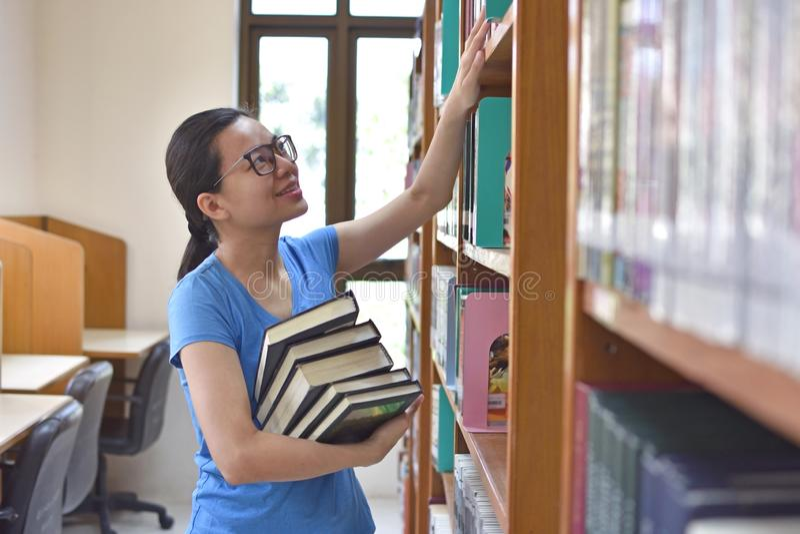 Estudiante universitario de sexo femenino que toma el libro del estante en biblioteca foto de archivo libre de regalías