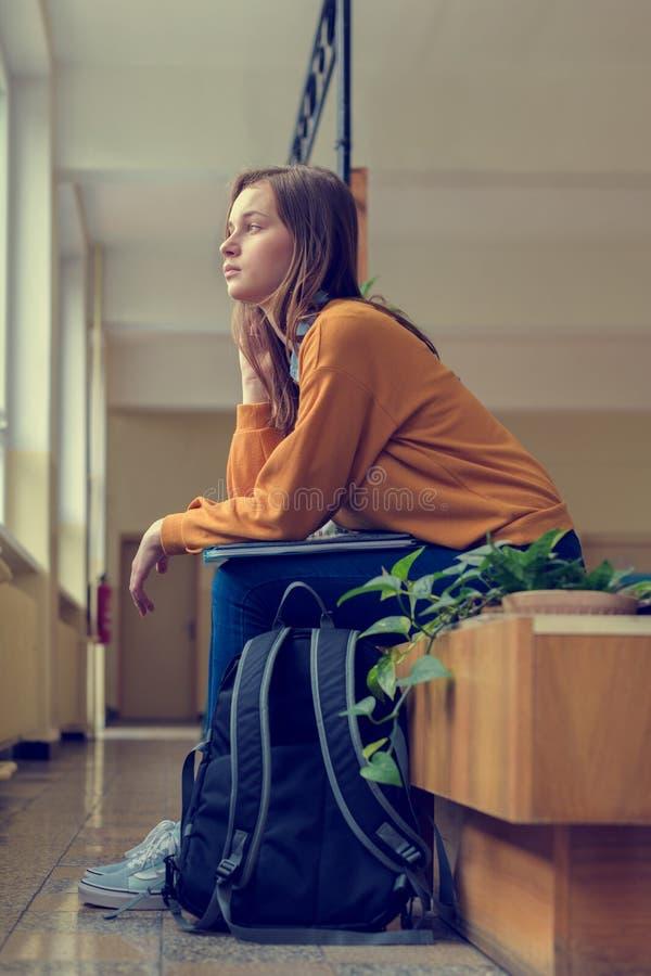 Estudiante universitario de sexo femenino solo deprimido joven que se sienta en el vestíbulo en su escuela Educación, concepto qu imagen de archivo