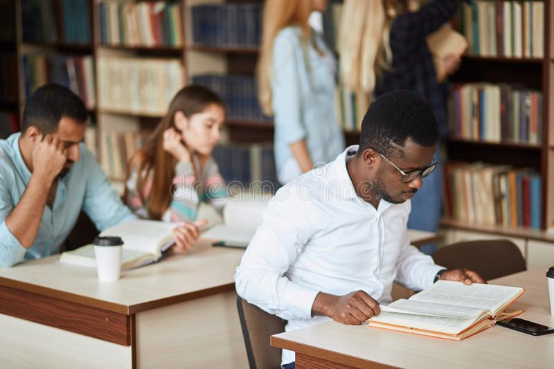 Estudiante universitario de sexo masculino afroamericano que se prepara para los exámenes en la biblioteca fotos de archivo libres de regalías