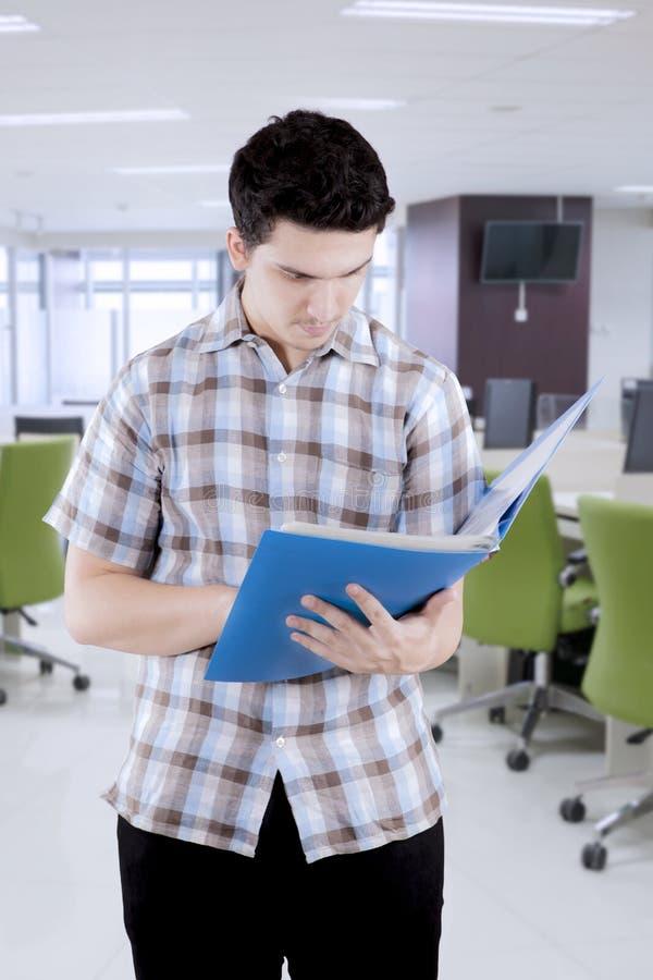 Estudiante universitario de sexo masculino con papeleo en biblioteca fotografía de archivo libre de regalías