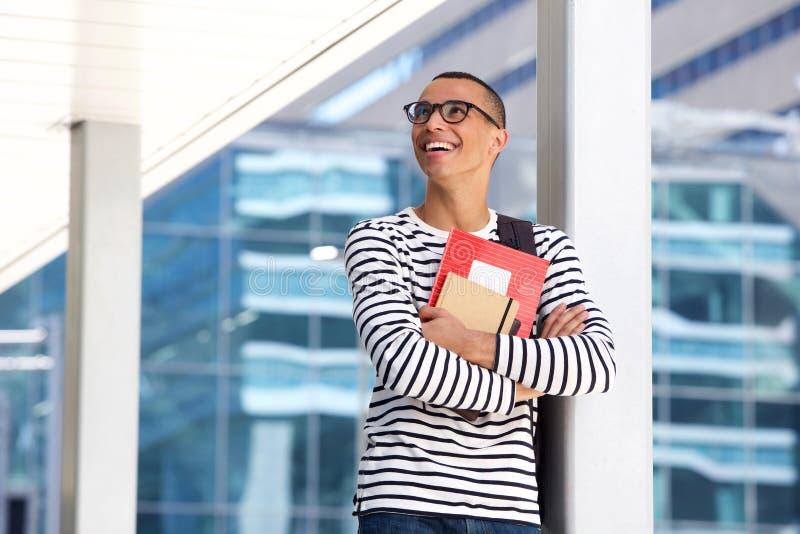 Estudiante universitario de sexo masculino feliz con los vidrios y los libros que se colocan en campus imagenes de archivo