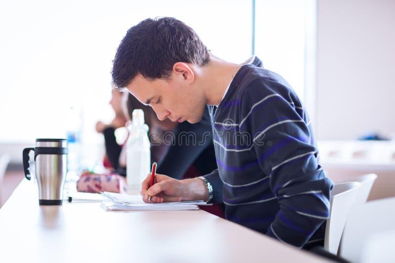 Estudiante universitario de sexo masculino joven, hermoso que se sienta en una sala de clase por completo foto de archivo