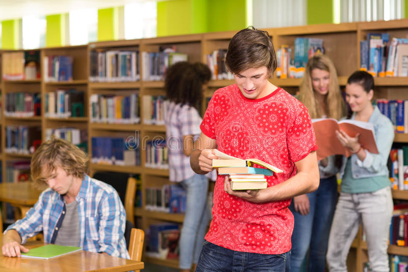 Estudiante universitario de sexo masculino que sostiene los libros en biblioteca fotografía de archivo