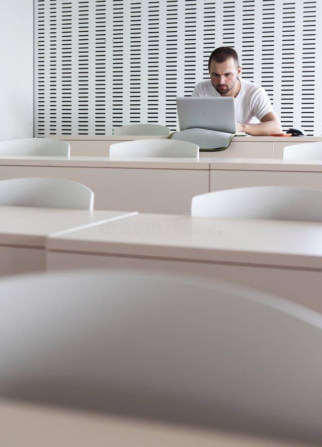Estudiante universitario de sexo masculino que trabaja en su computadora portátil fotografía de archivo