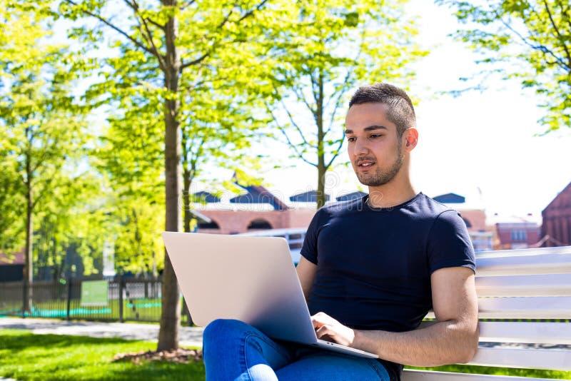 Estudiante universitario del hombre joven en línea que aprende vía el ordenador portátil, sentándose en un banco en un campus imágenes de archivo libres de regalías
