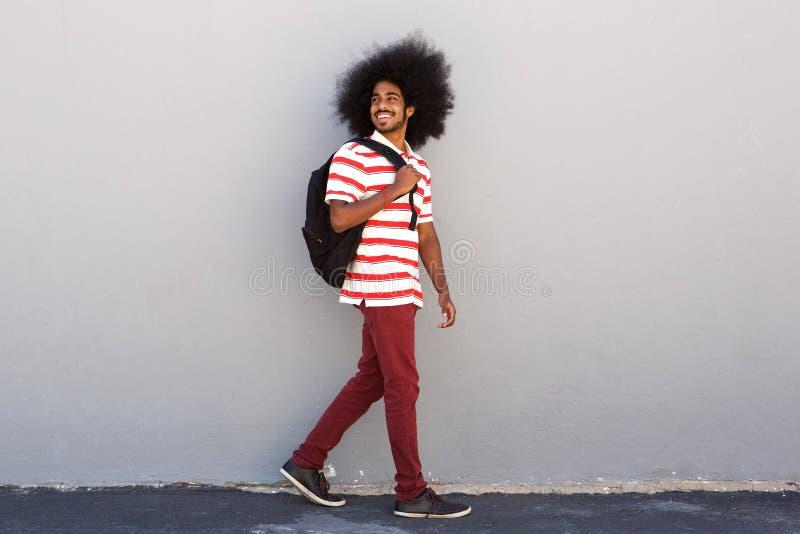 Estudiante universitario feliz con caminar del bolso imagenes de archivo