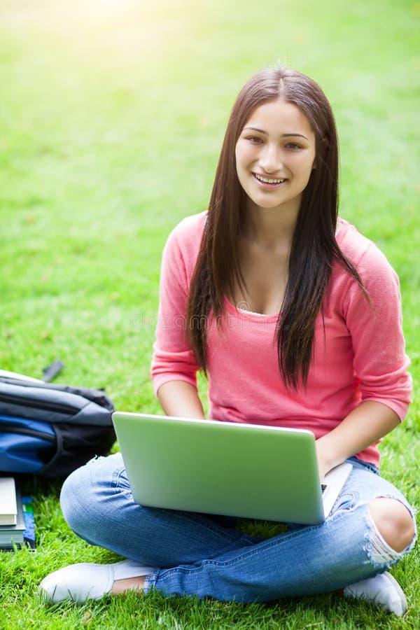 Estudiante universitario hispánico con la computadora portátil foto de archivo libre de regalías
