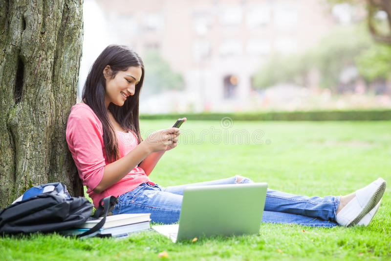 Estudiante universitario hispánico texting foto de archivo libre de regalías