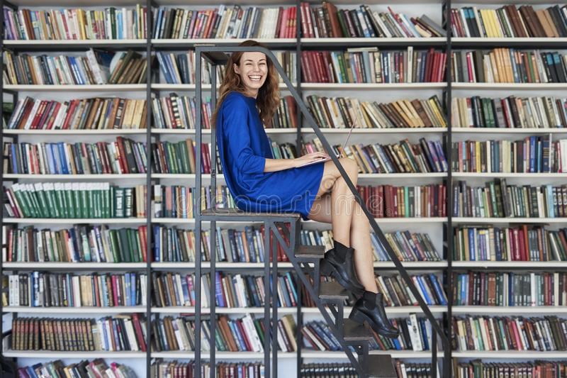 Estudiante universitario joven hermoso que se sienta en las escaleras en la biblioteca, trabajo de risa en el ordenador portátil  fotografía de archivo libre de regalías