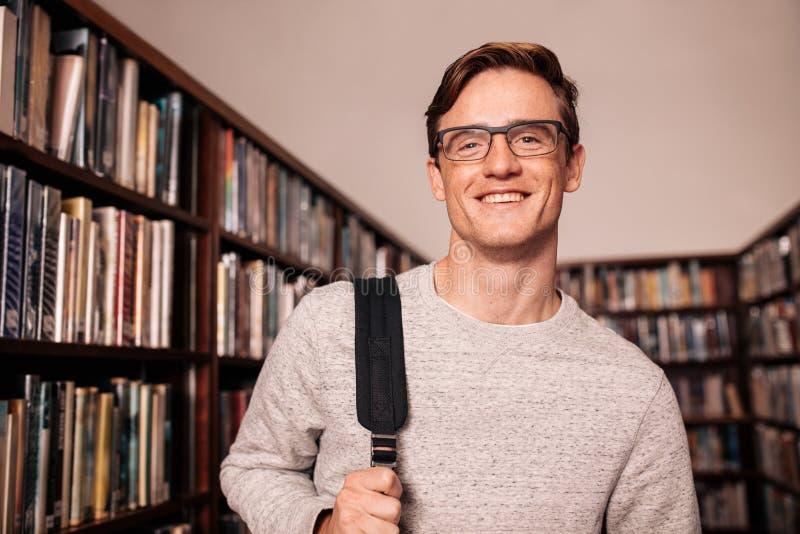 Estudiante universitario joven que se coloca en biblioteca imagenes de archivo