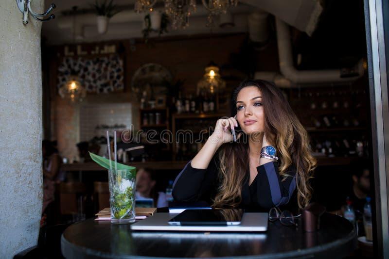 Estudiante universitario magnífico joven de la mujer que habla vía smartphone mientras que se sienta en cafetería después de estu fotos de archivo libres de regalías