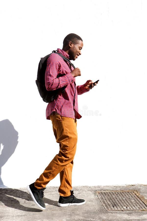 Estudiante universitario que camina con el bolso y el teléfono móvil imágenes de archivo libres de regalías