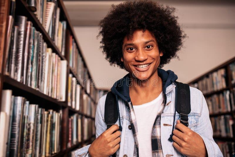 Estudiante universitario que se coloca en biblioteca fotos de archivo libres de regalías