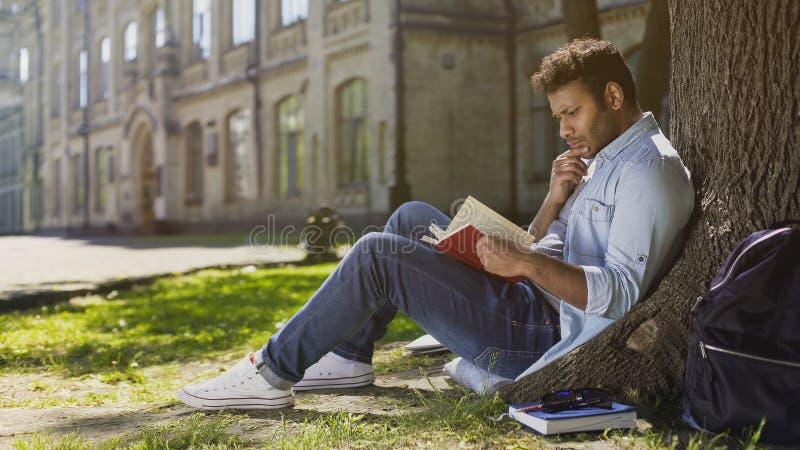 Estudiante universitario que se sienta debajo del libro de lectura del árbol con el diagrama conmovedor, absorbido foto de archivo