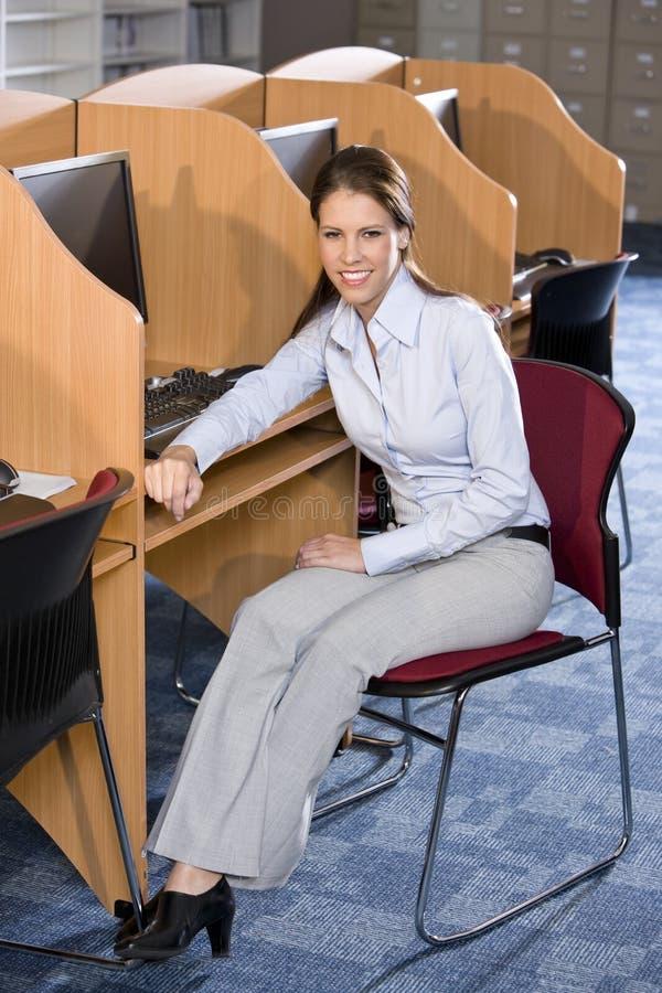 Estudiante universitario que se sienta en el ordenador en biblioteca imagenes de archivo