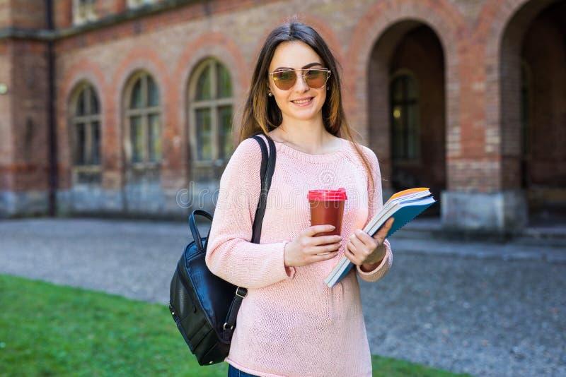 Estudiante universitario que sonríe con café y la bolsa de libros en campus con el espacio de la impresión imagen de archivo libre de regalías